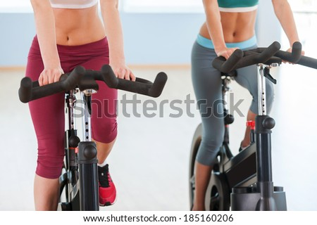 Girls on exercise bikes. Cropped image of two young women in sports clothing exercising on gym bicycles - stock photo