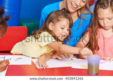 Girls painting in art class in elementary school with teacher - stock photo