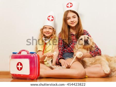 Girls play cute doctors bandaging their pet dog - stock photo