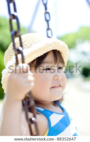 Girls play on the swing in the park - stock photo