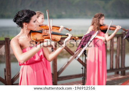 Girls plays violin outdoors near the river - stock photo