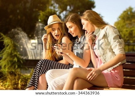 girls read the message in phone. it is photographed in the open air - stock photo