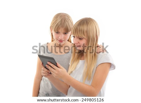 Girls reading a funny ebook with a tablet device in front of a white background - stock photo