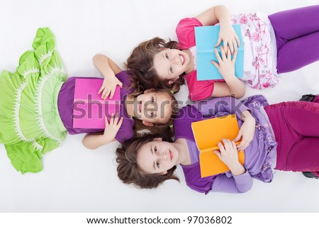 Girls reading and studying afternoon - laying on the floor with books - stock photo