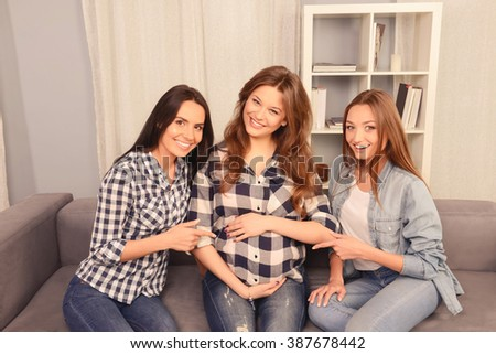 Girls sitting on sofa and touching belly of their pregnant girlfriend