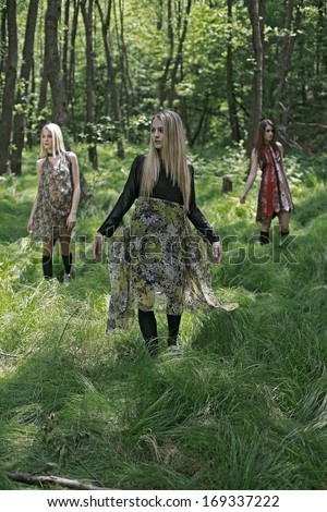 girls standing in the green woods, beautiful girls in a tall forest grass  - stock photo