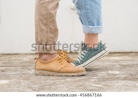 girls stands on tiptoe to kiss her man - Close up on shoes