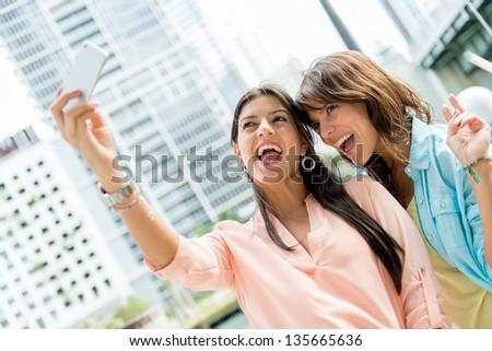 Girls taking a picture of them selves with the phone - stock photo