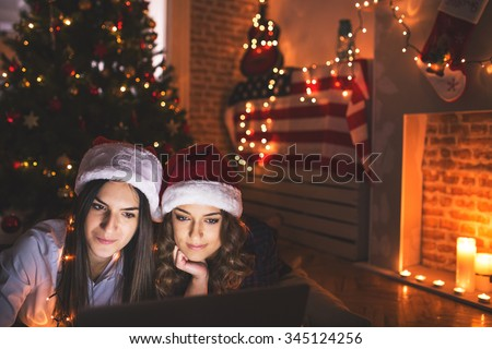 Girls using laptop together in front of a Christmas tree wearing Santa's helper hat. Depth of field, selective focus  - stock photo