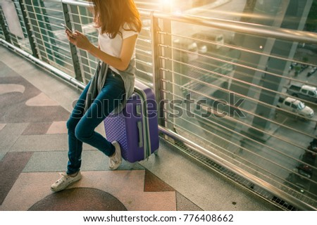 girls using smartphone checking flight or online check-in at airport together, with luggage. Air travel, summer holiday, or mobile phone application
