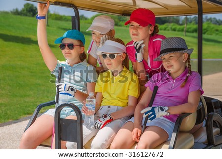 Girls walking in golf car at golf course at summer day - stock photo
