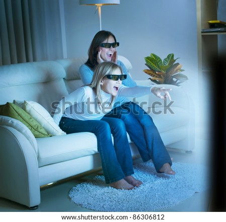 Girls watching 3d film on TV - stock photo