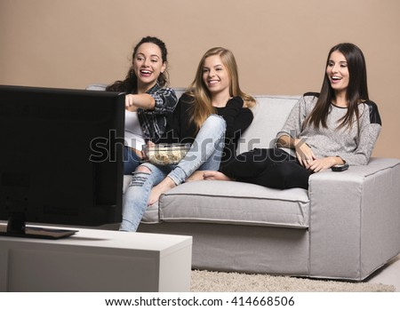 Girls watching movies with popcorn - stock photo