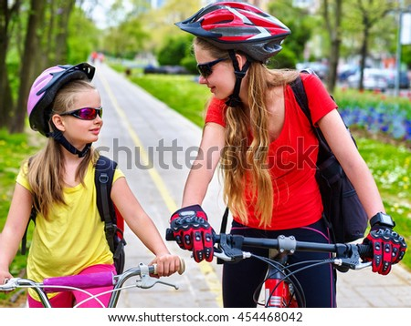 Girls wearing bicycle helmet and glass with rucksack ciclyng bicycle. Girls children cycling on yellow bike lane. Bike share program save money and time at city street. Girls talking to each other.
