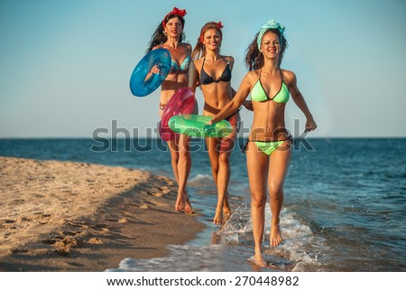 Girls wearing  bikini with lifebuoys on beach