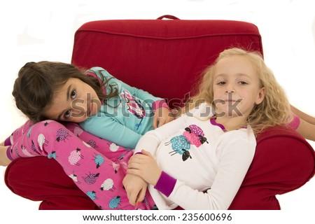 Girls wearing winter pajamas sitting red chair - stock photo