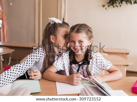 Girls whispering in school at the desk. Students