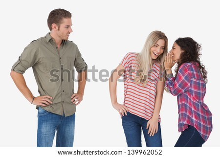 Girls whispering secrets and leaving man out on white background