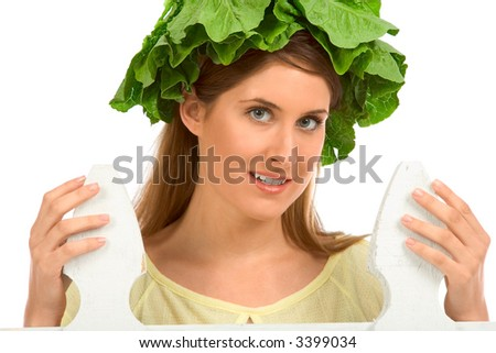 Girls with lettuce instead of hat by the white fence - stock photo