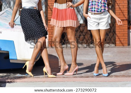 girls women friends with sexy tanned legs standing  - stock photo