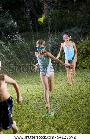 Girls, 7 years, in swimsuits playing and splashing in sprinkler, focus on girl in middle - stock photo