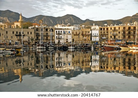 Girne harbour with boats and houses and reflections Marina of Kyrenia in Northern Cyprus - stock photo