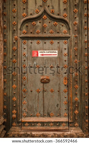 Girona, Catalonia, Spain - August 18, 2015: Medieval door. Girona. Old metal-embossed green wooden door with sign pointing to visitors' entrance, Cathedral of Santa Maria, Girona, Spain,