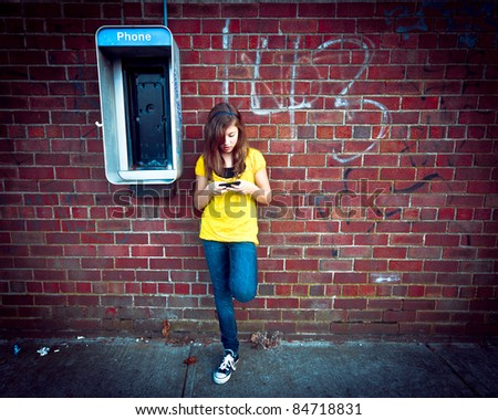 Gitty image of a girl texting on her cell phone next to an old out of service payphone, against a grungy urban wall