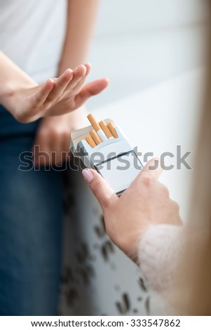 Give me. Close up of cigarettes in hands of man giving them to girl going to smoke - stock photo