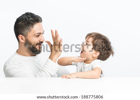 Give me high five, father and son looking happy - stock photo