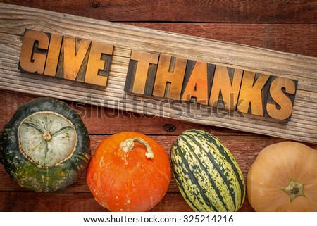 give thanks - Thanksgiving concept - word abstract in letterpress wood type over a grained cedar plank against rustic barn wood with winter squash - stock photo