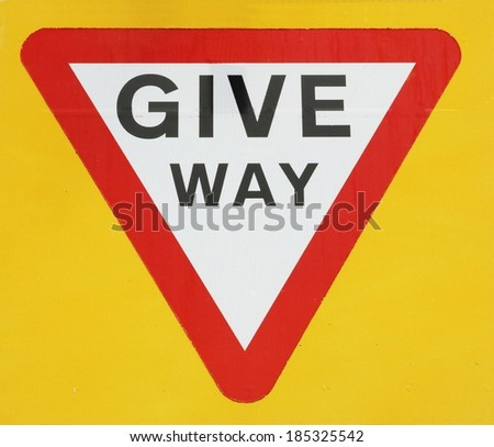 Give Way Sign Against A Yellow Background.  - stock photo