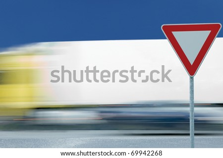 Give way yield road traffic sign and motion blurred truck in the background - stock photo