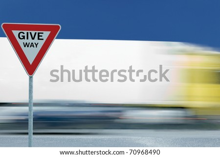 Give way yield road traffic sign and motion blurred truck in the background