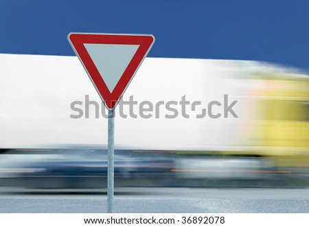 Give way yield road traffic sign, truck in the background - stock photo