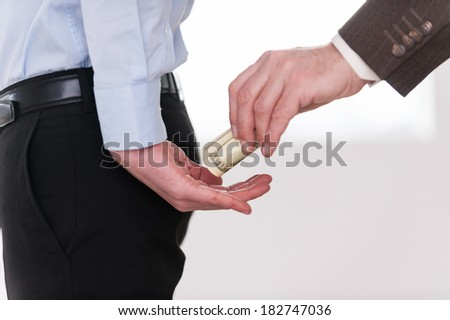 Giving a bribe. Close-up of businessman giving money to another man in formalwear