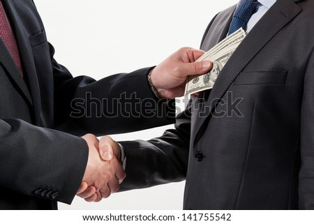 Giving a bribe into a pocket - closeup shot - stock photo