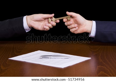Giving a golden key after signing a contract - stock photo