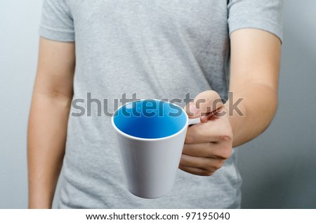 Giving a white and blue cup of coffee - stock photo