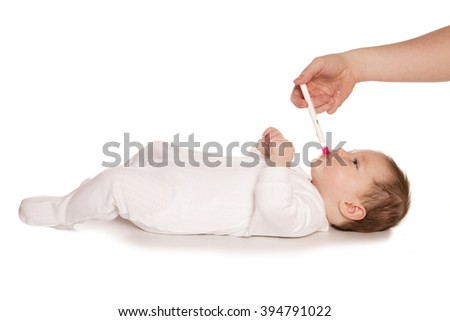 Giving baby medicine white background - stock photo