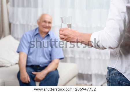 Giving care. Youthful grandson holding glass with water on background of his old grandfather. - stock photo