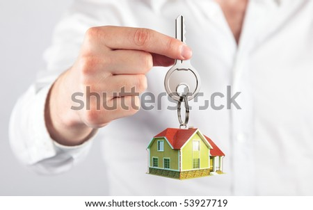 giving house key with a keychain house model form - stock photo