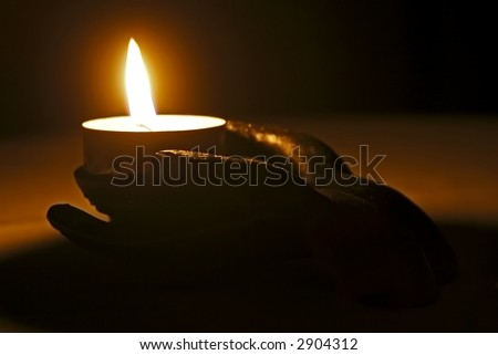 Giving the light: Hand made from stone holding a candle