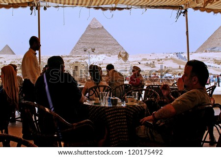 GIZA, EGYPT  - APRIL 27 2007:Tourists dinning in a cafe at the Pyramids of Giza, Egypt. The number of tourists visiting Egypt dropped by more than a third since the Egyptian revolution on Jan 25 2011