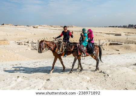 GIZA, EGYPT - NOV 23, 2014: Unidentified Egyptian man and two tourists ride horses in  Giza Necropolis, Egypt. UNESCO World Heritage - stock photo