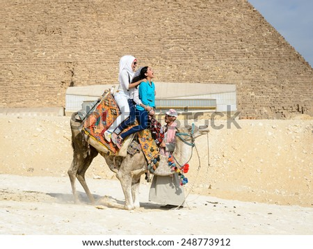 GIZA, EGYPT - NOV 23, 2014: Unidentified tourists ride a camel at Giza Necropolis, Egypt. UNESCO World Heritage