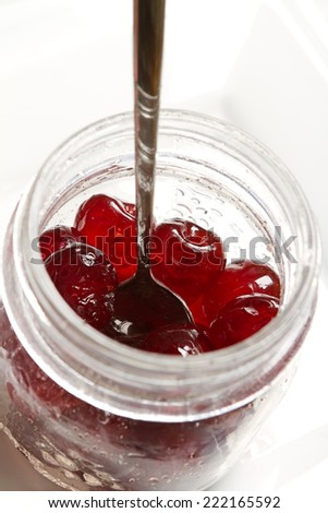 Glace cherries ingredients in a vintage jar on white background - stock photo