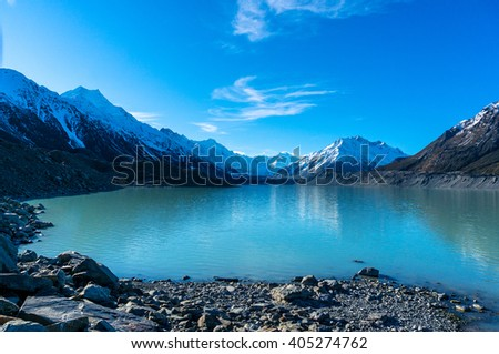 Glacier and lake with turquoise blue water and mountains landscape. Winter mountain landscape with glacier and lake. Tasman glacier, Aoraki - Mount Cook National Park, New Zealand - stock photo