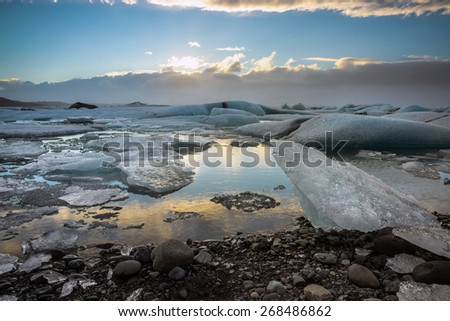 Glacier ice lagoon during sunset in Jokullsarlon, Iceland. The glacier breaks up into ice blocks in the lagoon before flowing out to sea as icebergs.