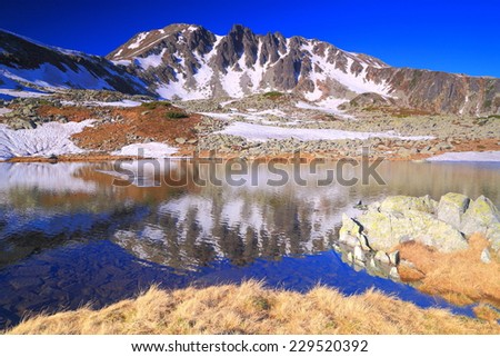 Glacier lake reflects mountains early in the morning - stock photo